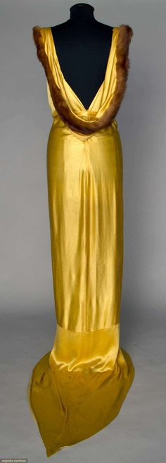 """YELLOW SATIN EVENING GOWN, 1930s : Slinky trained gown, sleeveless, a-symmetrical neckline, very low cut back w/ floating fur trimmed panel, self fabric belt, W unbelted 30"""", H 40"""", L 64""""-85"""", (soiling at hem line on train) excellent. Augusta Auctions"""