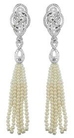 Earrings from Garrard's Entanglement collection with a delicate bead tassel of pearls below a gold and diamond knot.