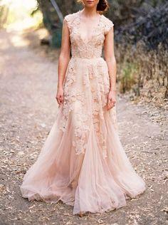 Romantic, blush wedding dress with a V-neckline and flower appliqués by Reem Acra.