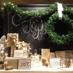 love the chalk board with the green garland - shop display idea  love the chalk... but with presents around it
