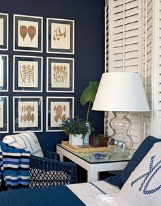 """Benjamin Moore """"old navy"""" paint makes a wonderful backdrop for this great room. The white brightens it. Shutters & the framed prints look so good together."""
