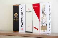 A selection of champagne cardboard boxes. From left to right: Pol Roger, Taittinger, Taittinger, G.H. Mumm, and Louis Roederer.