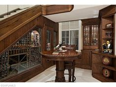 Custom wine room and climate controlled cellar under the stairs.  On Dunberry Dr in Quail West | Naples, Florida