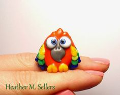 Ode to Peaches, the sun conure parrot.  A lampwork glass bead by Heather Sellers.