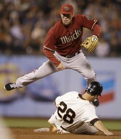 Arizona Diamondbacks' Aaron Hill hops over San Francisco Giants' Buster Posey (28) after a throw to first base for a double play in the sixth inning of a baseball game Wednesday, Sept. 10, 2014, in San Francisco. Pablo Sandoval was out at first base. (AP Photo/Ben Margot)