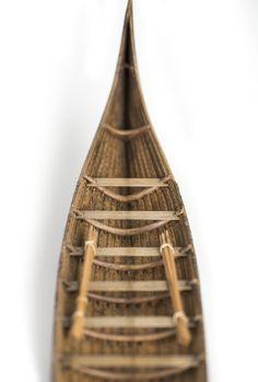 """Fartygsmodell av oxelträ, rekonstruktion av """"Stora Kvalsundsbåten, utgrävd 1920"""", daterad till 400-700 e.Kr.. Skrov utfört i två halvor med limfog genom köl och stävar. Bordläggningen skuren på såväl in- som utsidan. Klamparna på borden pålimmade. Håarna av lövträkvistar, med självvuxen knagge, fastbundna med svartoxiderad suturtråd. Skrovet betsat i tjärfärg."""