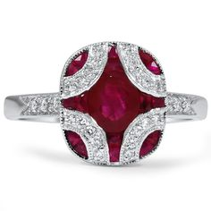 this Art Deco setting in white gold glimmers with an oval shaped natural ruby accented by sixteen French cut natural ruby accents and twenty-six round brilliant diamond accents