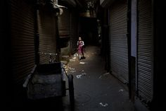An Indian schoolgirl walks through a darkened alley in New Delhi, India, on August 28, 2014. Alone, she is in danger of being attacked, raped or killed, everyday occurrences for girls and women in India. (AP Photo/Bernat Armangue)