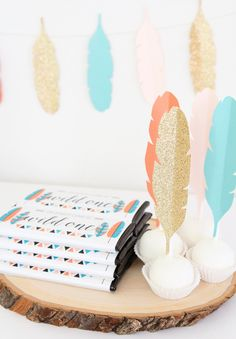 Wild One Tribal 1st Birthday Party | Personalized Candy Bar Wrappers from Sweet Paper Shop | DIY Paper Feather Garland & Cake Pop topper | Read about it on our blog!