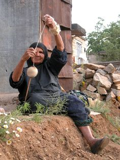 Look at the way she has wound the copp - it's round like a ball!  Unusual in shape yet if she has secured the beginning of the yarn away from the copp, she  can get to both ends of the yarn for plying.     painstaking grandmother - Paaveh, Kermanshah spinning with a high whorl spindle