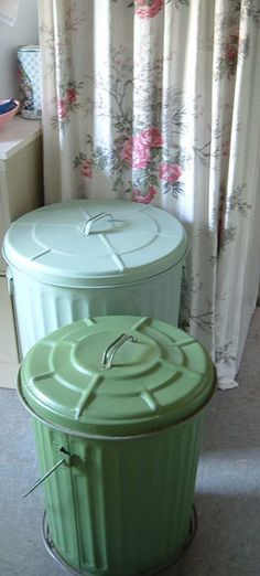 Galvanized metal cans, spray painted in shades of green to hide dog food, laundry, etc.. - I like this idea!