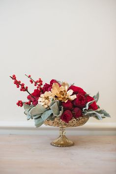 A deep-red centerpiece with garden roses, soft-grey dusty miller leaves, gold-painted succulents, and ilex berry branches | Brides.com