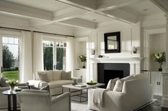 Shope Reno Wharton — monochromatic,wall of transom windows, living room transom windows,floor to ceiling curtains, white curtains, white drapes, coffered ceiling, fireplace alcoves, built ins, black and white fireplace, fireplace mirror, black fireplace