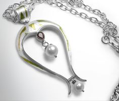 Pearl, garnet, pure silver and pure gold, wet with a small diamond