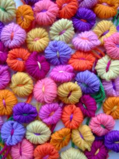 Little wool flowers in summery colours. I made these to decorate a tea cosy in the knitting book, and may just have got carried away with quantities as they looked so nice, scattered like flower heads, on the carpet. Inchies, Yarn Flowers, Shabby, Yarn Bombing, How To Purl Knit, Craft Materials, Embroidery Techniques, Yarn Crafts, Fabric Crafts