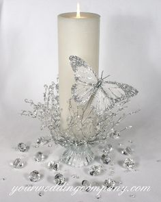 A white pillar candle decorated with an acrylic ice-drop garland and a silver feather butterfly.  This design can be a unity candle or a reception centerpiece.vendors: Your Wedding Company