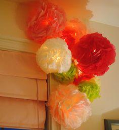 Tissue paper pom poms on a string of lights