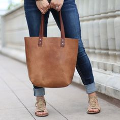 The Ashley Tote Fine Leather Handbag The Ashley Tote is our first tote bag and is made right here in our shop with the finest of Full Grain American leathers. We hand-pick our leather hides from a local tannery for a rustic look and feel. This gift will be used and loved for a lifetime! …