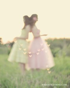 Taken with a lens cover with a heart punched in the middle.  Girls are holding a string of lights.