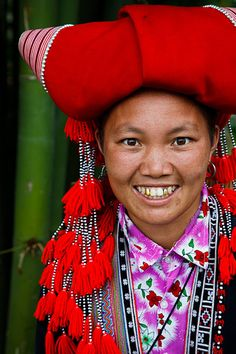 Vietnam   Portrait of a Red Dzao hill tribe woman wearing traditional clothing and headdress, stood by bamboo in a small village near to Sapa called Lao Chai   © Kimberley Coole