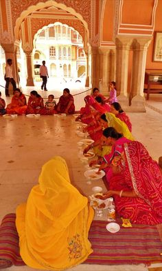 Women eat a daily meal cooked and offered by volunteers. Amer Fort, Jaipur, Rajasthan, India