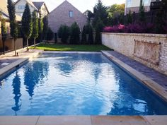 Light-colored coping frames the pool's edge and mirrors the tones from the brick retaining wall against the rear of the yard.