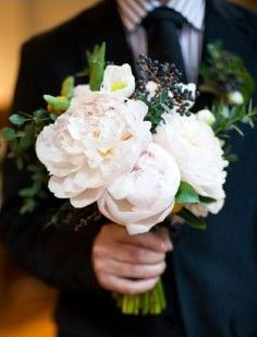 The bridesmaids will carry bouquets of white hydrangeas, white astilbe, blue viburnum berries, blush spray roses, and seasonal greenery wrapped in navy ribbon with the stems showing.