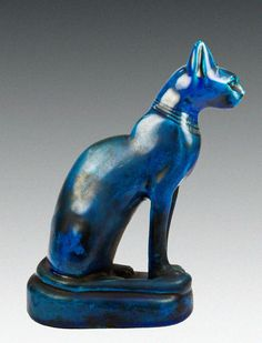 "Egyptian faience cat, 26th Dynasty. ""Vivid blue faience cat seated on a base and wearing a collar. Sacred animal to the sun god Ra and Bastet. The earliest Egyptian depiction of the cat took the form of three hieroglyph symbols, each representing seated cats... inscribed on a stone block that may date as early as 2278-2184 BCE."" Third of three photos. http://sadigh.weebly.com/featured-artifacts/sadigh-gallerys-ancient-egyptian-faience-cat-45639"
