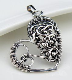 A beautiful symbolic wire wrapped heart pendant made with oxidized sterling and fine silver. In the heart you will find a fine silver fetus. atelierblaauw