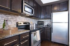 A beautifully decorated dark wood stainless steel kitchen at Alta Heights Luxury Houston Apartments.
