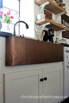 A beautiful hammered apron front farmhouse copper sink centers this farmhouse style kitchen. It really pops against the white cabinets, subway tile and open shelving. Apron Front Kitchen Sink, New Kitchen Cabinets, White Cabinets, Kitchen Countertops, Kitchen Aprons, Copper Farmhouse Sinks, Copper Kitchen, Farmhouse Style Kitchen, Farmhouse Decor