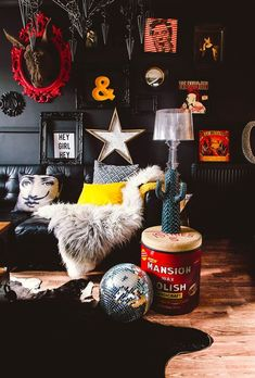 a pop art living room with black walls and furniture and lots of artworks and decorations to make it really eye catching