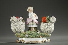 A double porcelain inkwell signed Jacob Petit with polychrome young girl sitting on a rock, a shawl over her shoulders, arms crossed on her chest. His double basket fixed on...