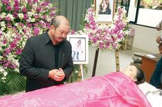 Thai woman in her open casket during her funeral.