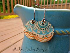Round handpainted leather and copper metal earrings. Turquoise and orange.