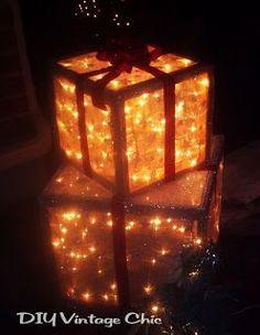 Große Geschenke aus einem Holzrahmen wurden mit Stoff umwickelt und mit Lichterketten gefüllt. Diese leuchten nun in einem warmen Licht.