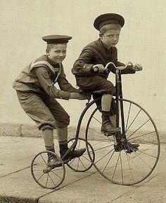 Two happy boys on a 1880's children's tricycle.