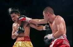 Chris John of Indonesia (R) lands a right hand on Chonlatarn Piriyapinyo of Thailand during their WBA super world featherweight title fight at the Marina Bay Sands in Singapore November 9, 2012. REUTERS-Edgar Su