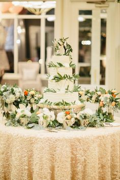 Wedding cake on antique silver stand surrounds by greenery and LOVE cups filled with flowers