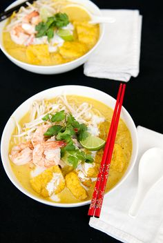 Malaysia Nyonya Cuisine: Curry Laksa - Coconut milk-based curry soup. [Main ingredients include tofu puff, fish stick, shrimp, cockle, long bean, and bean sprout. Some may include chicken. It is served with a spoonful of Sambal (chilli-based paste), half of a lime, and garnished with Vietnamese coriander.]