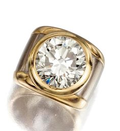 DIAMOND RING. The collet-set brilliant-cut diamond enhanced by a two-tone wide band, mounted in yellow and white gold,