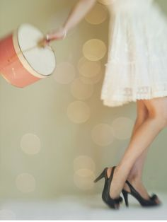 Stylish fashion photography - Girl in black heels, white lace dress and Hat Box, with soft bokeh background