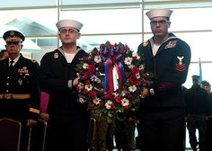 Seaman Steven Orick and Petty Officer 1st Class Steven LeGuillow participate in a wreath laying during the Pearl Harbor 75th Commemoration and World War II Remembrance Ceremony in Naval Station Everett Grand Vista Ballroom.
