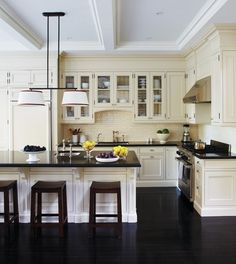 Exquisite dark wood flooring and dark countertop while everything else is creamy white.