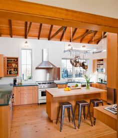 The new, open kitchen is the heart of the renovation, with views of the garden in every direction. The added kitchen and dining rooms fea...