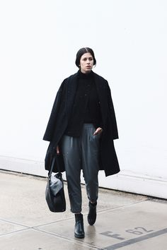 Elisa from the Fashion- and Lifestyleblog www.schwarzersamt.com is wearing a black woolen coat from H&M with grey loose fit pants vom RESERVED, a black daily bag from ZARA and high chelsea boots in black. It's a minimal and monochrome style in black and grey.