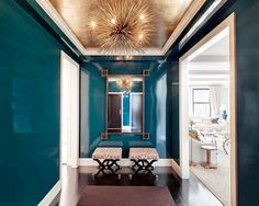 Gold foil wallpaper on the ceiling of this modern entryway/foyer with abstract light fixture