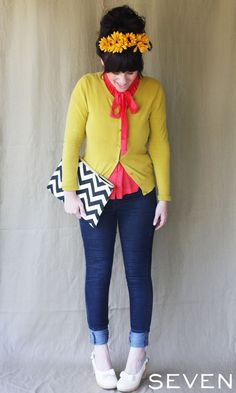Pea soup green sweater, coral tie blouse, sunflower head band, oversized black and white chevron clutch, dark wash denim, white bow embellished chunky heels