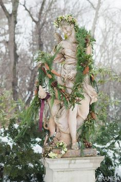 Statue draped in cedar and pine boughs with pinecones, hellebores, and ribbon.