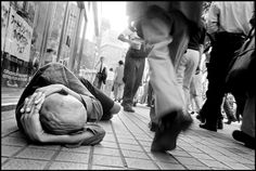 Bruce Gilden JAPAN. Tokyo. 1999. Homeless man sleeps in the streets while commuters pass by.